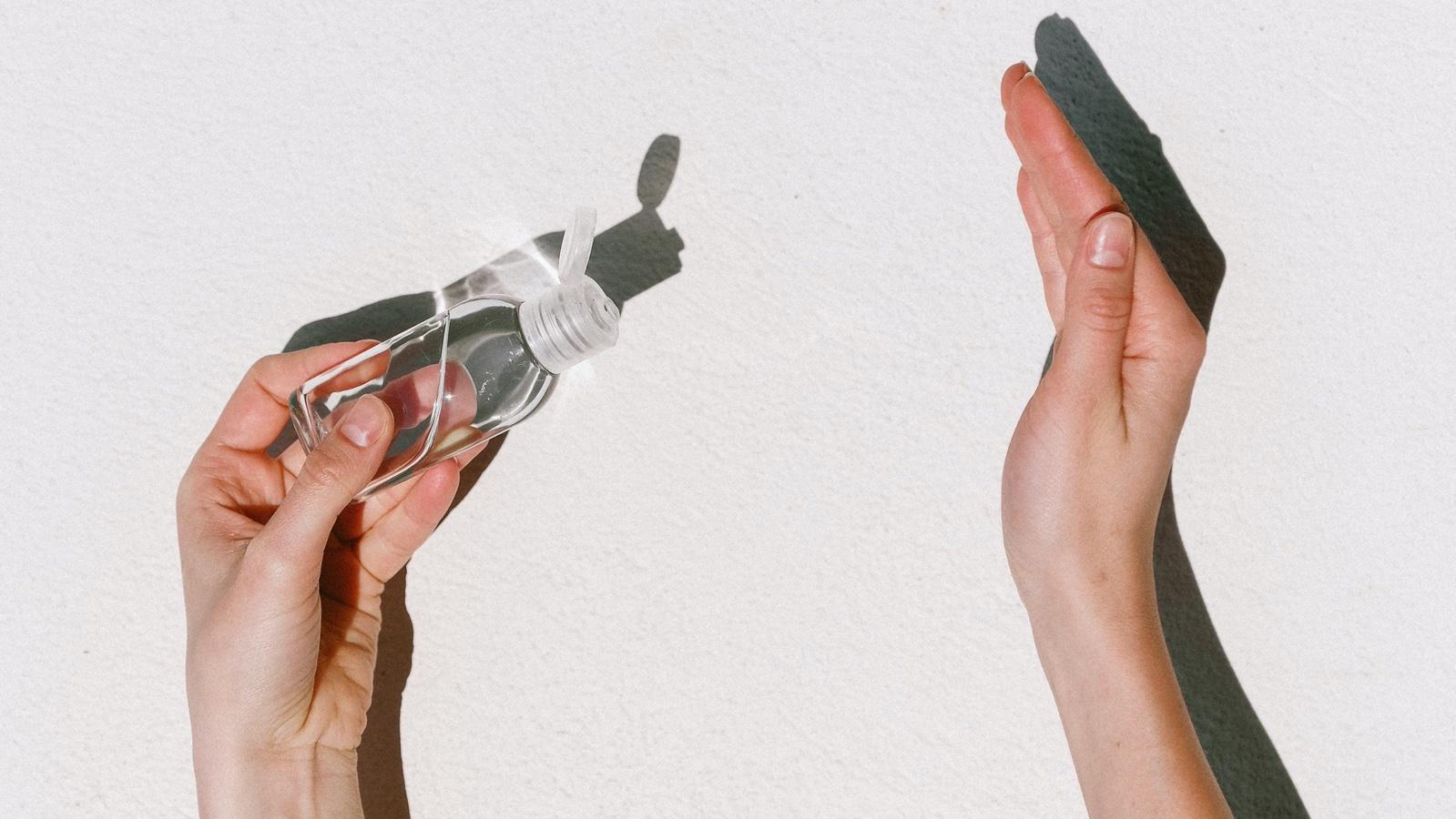 Pessoa passando álcool em gel na mão. Crédito: Pexels