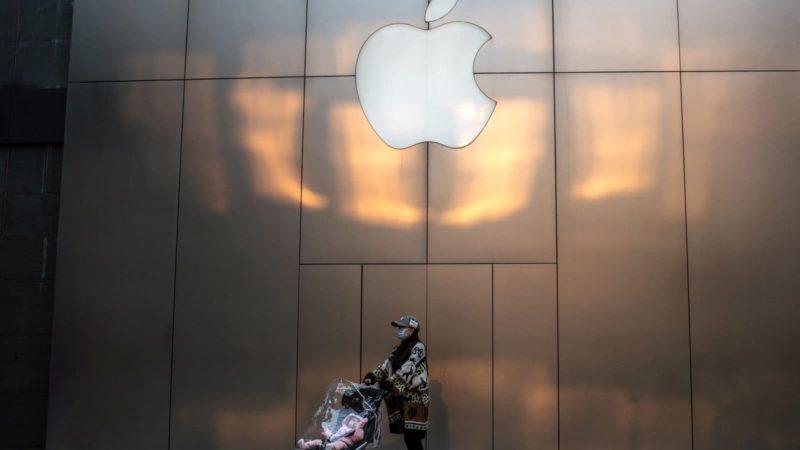 Pessoa com máscara e um carrinho de bebê sob fachada da Apple