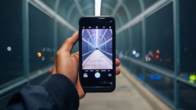 Uma mão esquerda segura um celular com o app de câmera aberto diante de uma passarela de pedestres.
