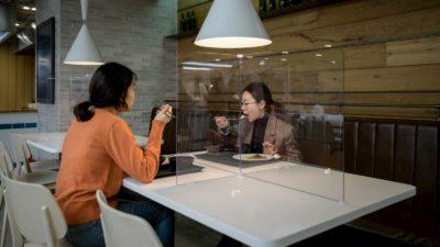 Pessoas comendo separadas por uma tela na Coreia do Sul