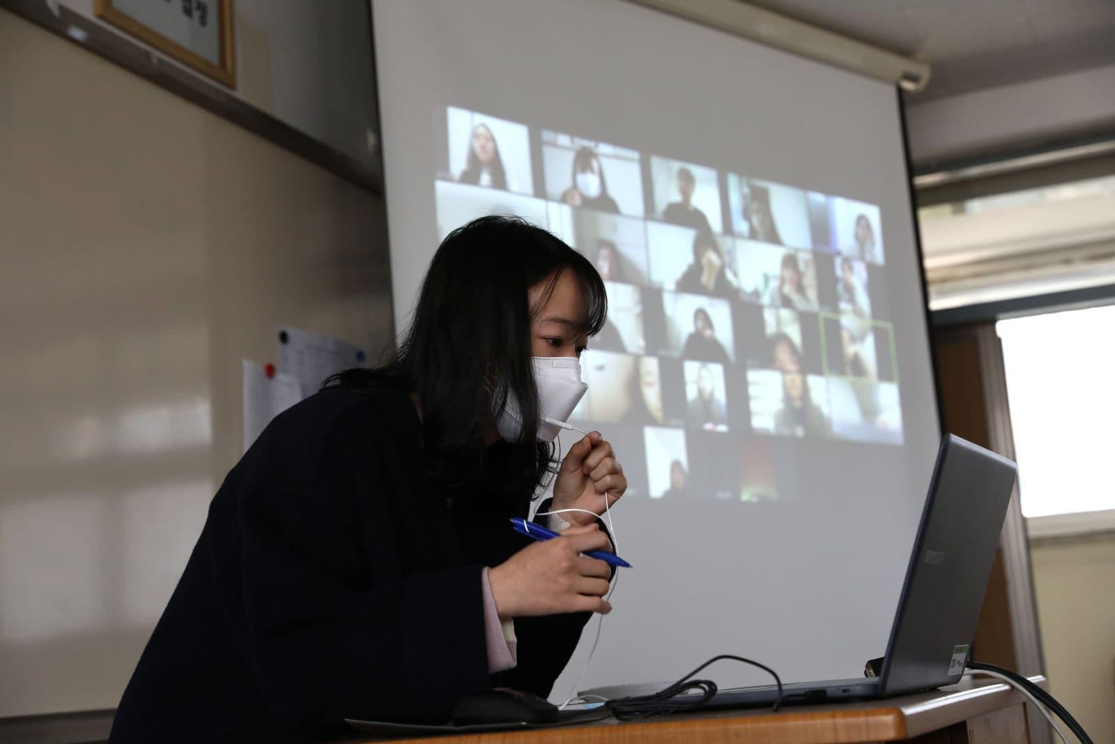 Professora usa uma máscara enquanto dá uma aula online em uma sala de aula vazia