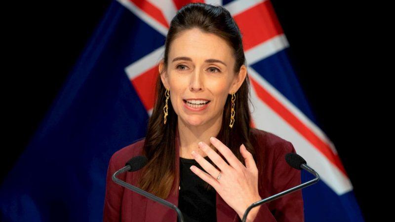 Primeira-ministra da Nova Zelândia, Jacinda Ardern, diante de dois microfones, com a bandeira do país ao fundo.