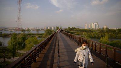 Uma mulher caminha ao longo de uma ponte perto do distrito de Yeouido, em Seul, Coréia do Sul.