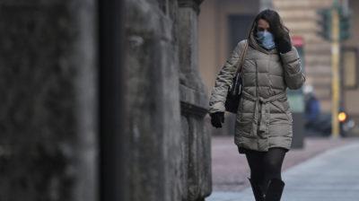 Mulher caminha em rua usando máscara de proteção facial. Crédito: Getty Images