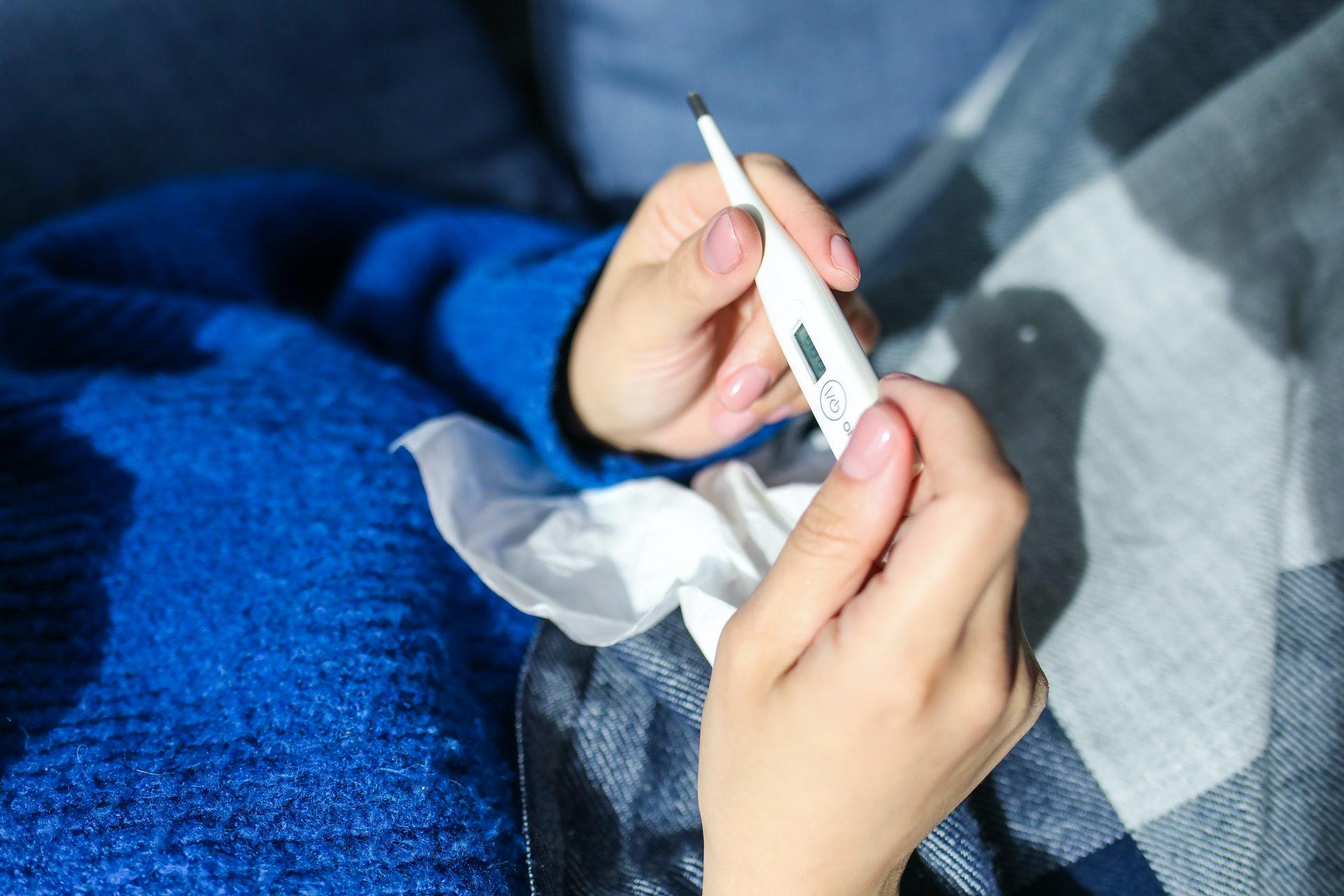 Pessoa conferindo temperatura com termômetro. Crédito: Pexels