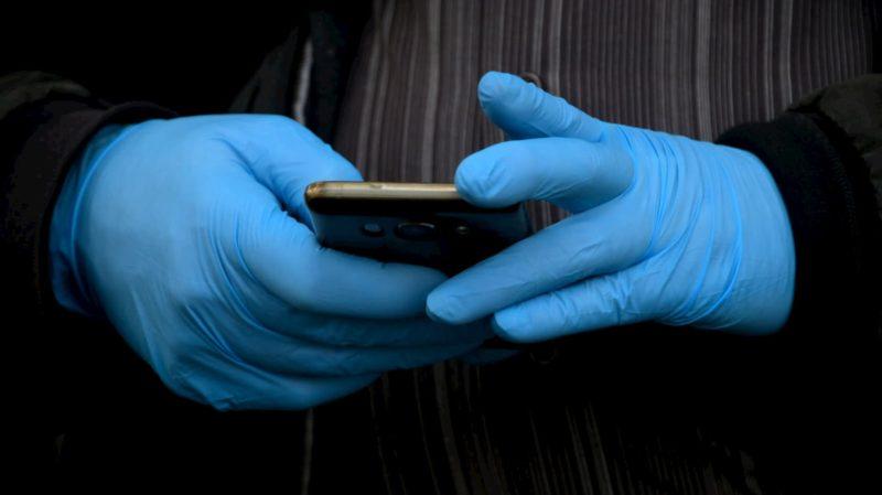 Pessoa com luvas mexendo no celular