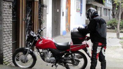 Motoboy mexendo no baú da moto na CIdade do México. Crédito: flickr/carlbcampbell/cc