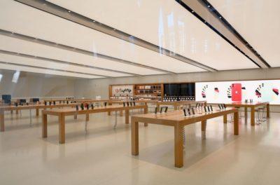 Loja da Apple fechada. Há várias mesas de madeira com produtos expostos. Ninguém está na loja.