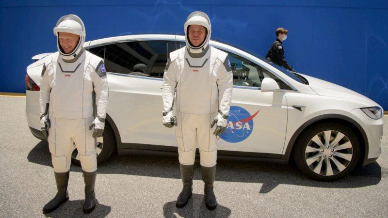 Os astronautas da NASA Douglas Hurley e Robert Behnken vestindo trajes espaciais SpaceX com um Tesla Model X atrás deles.