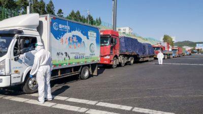 Funcionário usa equipamento de proteção e fala com caminhoneiro na saída de uma rodovia em Jilin, na província chinesa de Jilin, no dia 13 de maio de 2020.