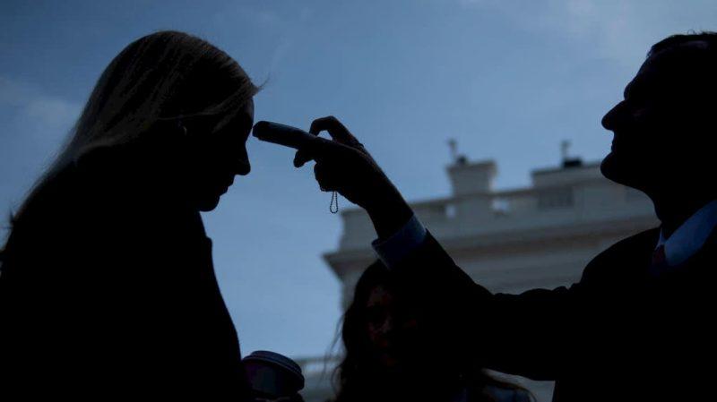 Mulher tem sua temperatura checada em frente a Casa Branca, nos EUA