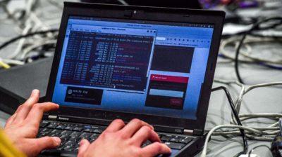 Laptop da Lenovo com tela exibindo códigos. Crédito: Getty Images