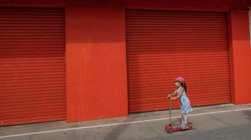 Garotinha de vestido azul e chapéu rosa anda de patinete em frente a um muro vermelho.