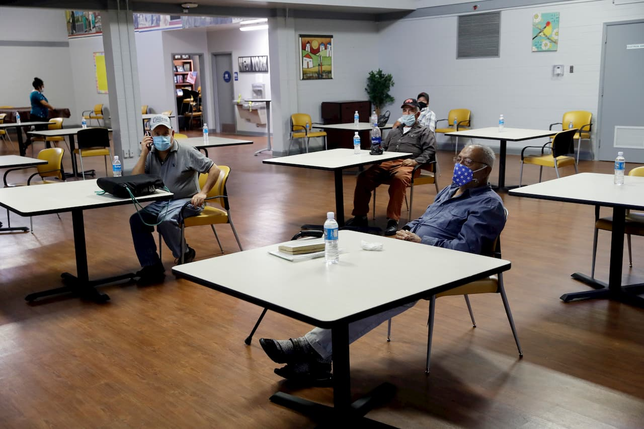 Vários homens sentados cada um diante de uma mesa em uma sala ampla. Todos usam máscaras.