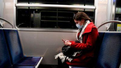 Mulher mexe no celular no metrô