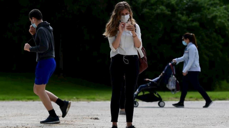 Mulher usa smartphone em espaço público enquanto está de máscara