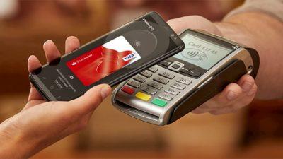 Pessoa pagando pelo celular com Samsung Pay
