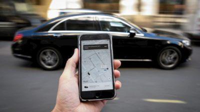 Pessoa segurando celular com app do Uber aberto