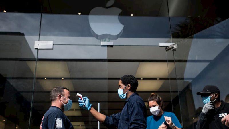 Funcionário verifica temperatura de um cliente na entrada de Apple Store