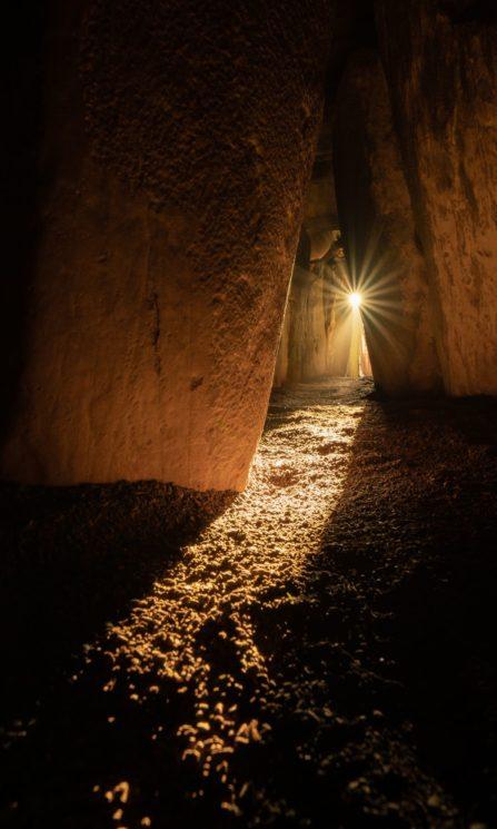 Foto de interior de tumba com o Sol entrando por um pequeno buraco ao fundo.