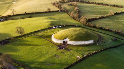 Foto de campo aberto com uma construção circular de bordas brancas e cobertura vegetal.