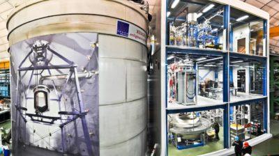 Foto do experimento XENON1T. À esquerda, uma construção circular alta, provavelmente um tanque. À direita, uma construção de três andares com paredes de vidro. Dentro dela, vários equipamentos metálicos cilíndricos e canos. Cada andar tem mais ou menos o dobro da altura de uma pessoa.