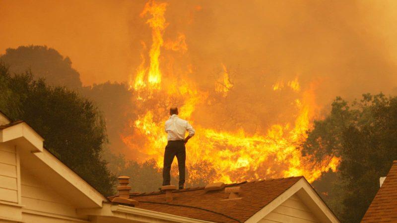Um homem em um telhado olha para as chamas que se aproximam do incêndio de Springs em maio de 2013 perto de Camarillo, Califórnia.