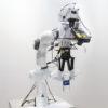 Robô com uma mão composta de duas placas segunrando uma garrafa de água de plástico. O robô também tem uma câmera apontada para sua mão.