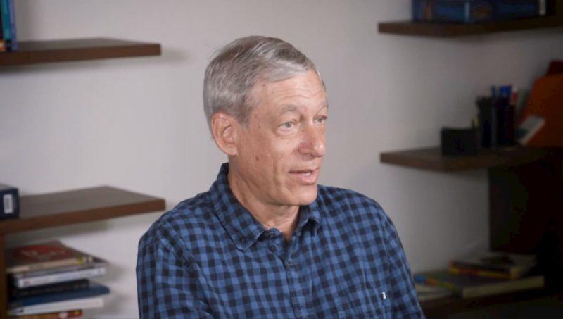 Marc Levoy, um senhor de cabelos brancos, pele branca e olhos claros. Ele está usando uma camisa azul xadrez e está no que parece ser uma biblioteca em sua casa.