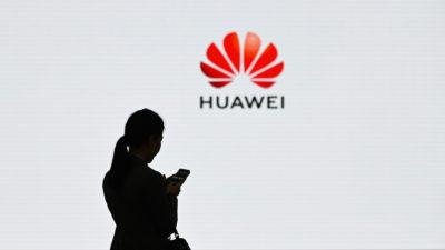 Mulher segurando smartphone é fotografada com o logotipo da Huawei. Crédito: Wang Zhao/Getty Images