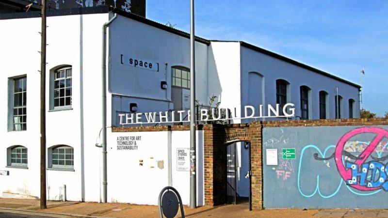 Edifício pintado de branco com um muro com grafites