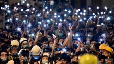 Protestantes em Hong Kong com as lanternas de seus celulares acesas.
