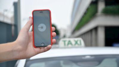 Pessoa segura celular com app da Uber em frente a um táxi