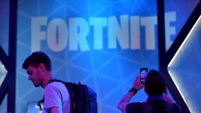 Logo do Fortnite ao fundo. À frente, dois rapazes com mochilas nas costas. Um dos rapazes tira foto do logo.