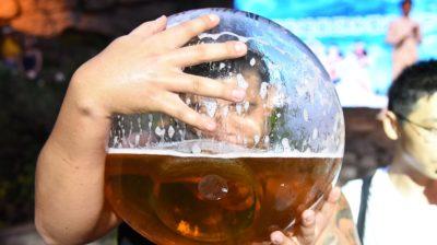 Homem bebendo cerveja em um copo gigante. Crédito: VCG/Getty Images