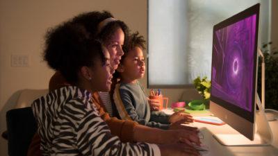 Mãe e duas filhas mexem em um iMac. Crédito: Apple
