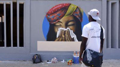Homem observa grafite em muro em que mulher está espirrando. Crédito: Seyllou /AFP (Getty Images)