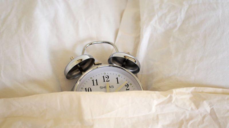 Despertador antigo sobre uma cama, coberto parcialmente com um lençol branco.