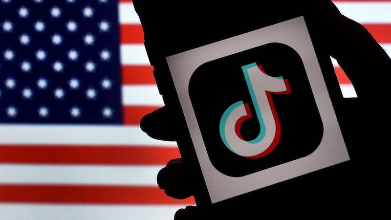 Smartphone com logo do TikTok com bandeira dos Estado Unidos ao fundo. Crédito: Olivier Douliery/Getty Images