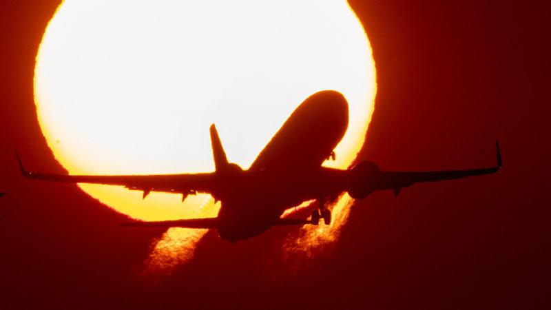 Avião voando com Sol radiante ao fundo. Crédito: AP