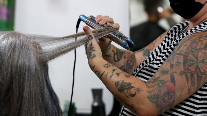 Cabeleireira alisa o cabelo de mulher em salão. Crédito: Justin Sullivan/Getty Images