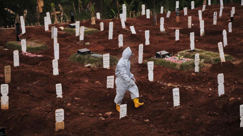 Funcionário de cemitério municipal caminha por área específica para suspeitos de morte por COVID-19 em Jacarta, na Indonésia. Crédito: Ed Wray/Getty Images