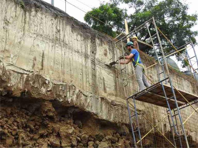 Homem em andaime com uma pá retira material de um muro rochoso.