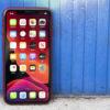 iPhone 11 vermelho diante de um fundo azul.