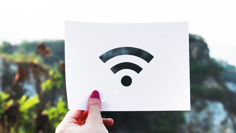 Mulher segurando papel com o símbolo do Wi-Fi. Crédito: rawpixel/Unsplash