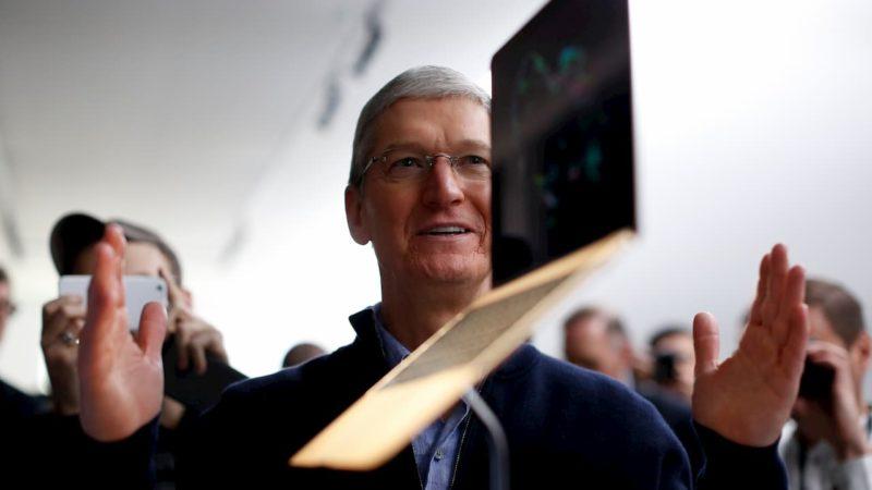 Tim Cook com os braços abertos diante de um MacBook suspenso no ar, provavelmente sob um apoio invisível em uma bancada de produtos.