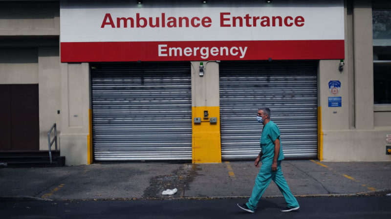 Médico caminha em frente a hospital no Brooklyn, em Nova York (EUA). Crédito: Spencer Platt/Getty Images