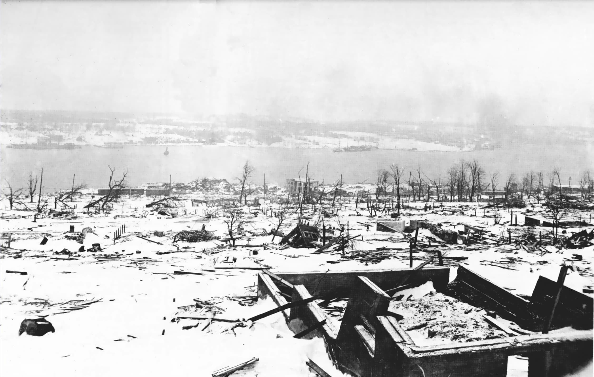 Imagem em preto e branco que mostra um rio e várias construções de madeira completamente destruídas.
