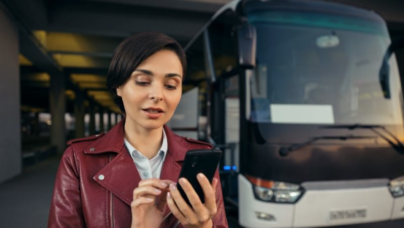 Imagem mostra mulher mexendo em um smartphone com um ônibus ao fundo. Crédito: BlaBlaCar