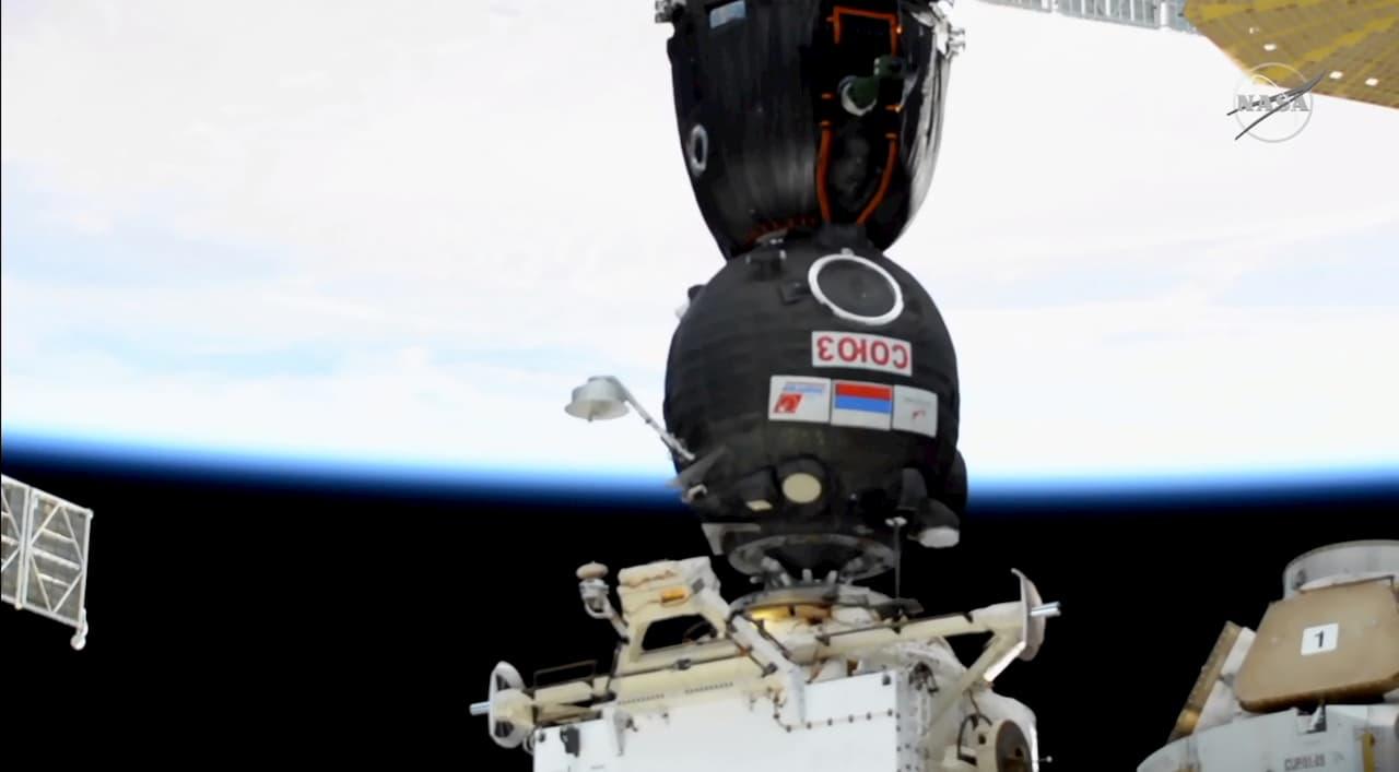 Cápsula preta com bandeira russa encaixada a um módulo no espaço.